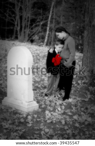 A young boy and girl grieve at a grave (color removed except for flowers) - stock photo