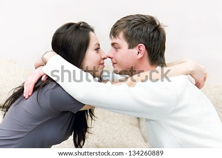 A young boy and girl look at each other while sitting on the couch - stock photo