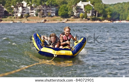 A young boy and girl riding a tube behind a boat. - stock photo