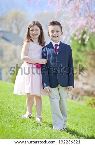 A young boy and girl standing outside portrait - stock photo