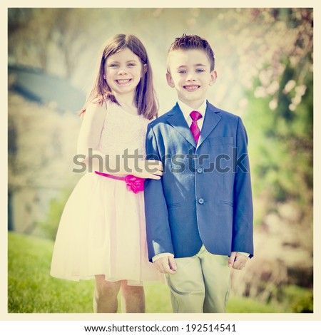 A young boy and girl standing outside portrait with Instagram effect filter - stock photo