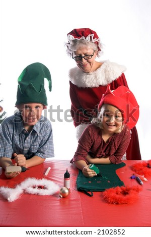A young boy and girl wearing elf hats and working with Mrs. Santa Claus on a Christmas craft project of decorating a stocking