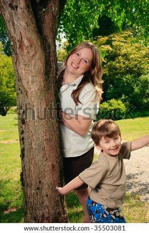 A young boy and his Mother having a good time under a tree