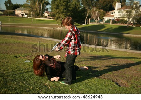 """a young boy and his mother play """"cops and robbers"""" in a park - stock photo"""