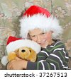 A young boy and his teddy both wearing santa hats enjoy a cuddle - stock photo