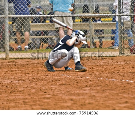 A young boy at bat ducking away from the ball as it comes close to his head. - stock photo