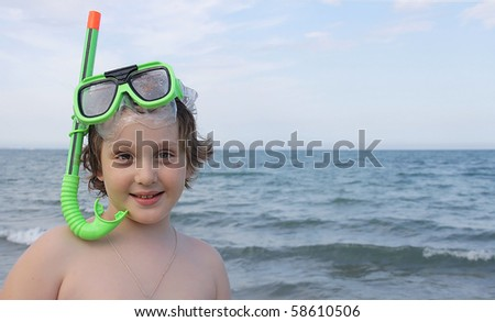 A young boy at the beach with snorkel. - stock photo