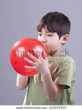 A young boy blows up a red baloon. - stock photo