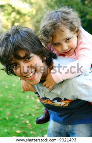 A young boy carrying his sister on his back as they play outdoor in the park - stock photo