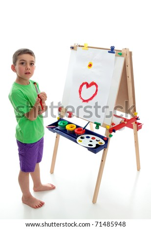 A young boy child stands by an easel with a beginning of a picture painted.  White background. - stock photo