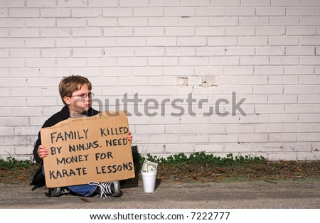 A young boy collecting funds for karate lessons. - stock photo