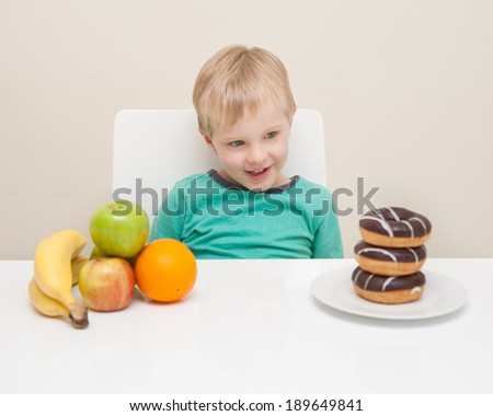 A young boy considers whether he will have a unhealthy doughnut or some healthy fruit.  The child is photographed against a white background