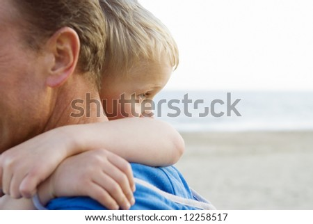 A young boy cuddles his father. - stock photo