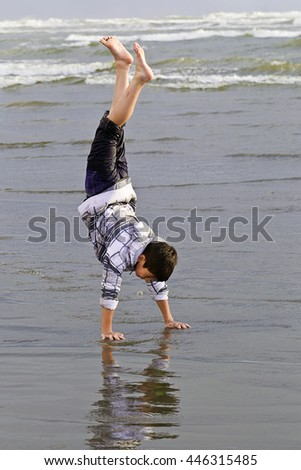 A young boy does a handstand in the wet sand at the beach.