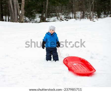 A young boy dressed for cold weather poses with his red sled in the snow during the winter season.  - stock photo