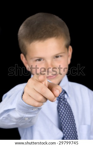 A young boy dressed up in a shirt and tie pointing at the camera, communicating his message to you.  Image was shot using a black backdrop and is not a cutout.  Focus is on index finger. - stock photo