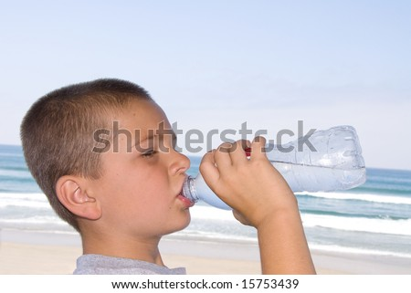 A young boy drinks bottled water on a hot day at the beach. - stock photo