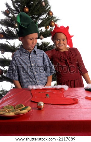 A young boy elf  laughs with embarrassment as a young girl elf puts her arm around him