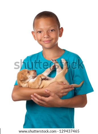 A young boy enjoys holding his puppy dog in his arms. - stock photo