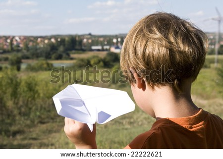 a young boy flying a paper plane - stock photo