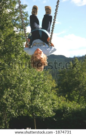 A young boy gets so high on a swing that he appears upside down. - stock photo