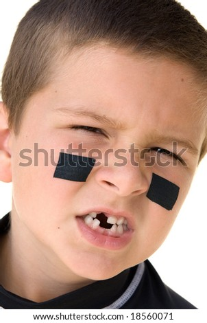 A young boy getting ready to play hockey snarls at the camera to show off his missing teeth. - stock photo
