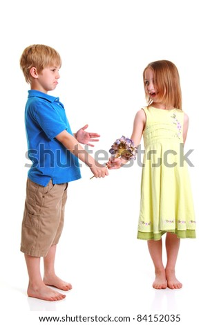 A young boy giving a young girl a flower - stock photo