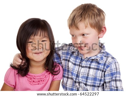 A young boy has his arm around a young girl.