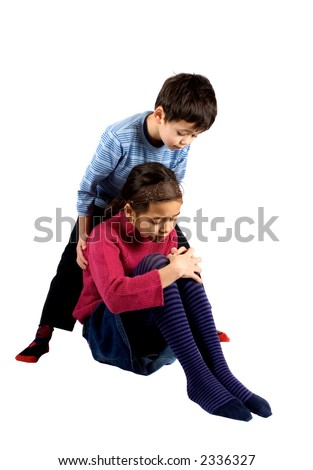A young boy helping his sister up after she fell over and hurt her knee. - stock photo