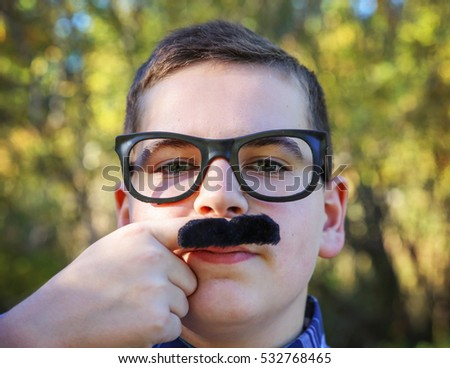 a young boy holding a finger mustache up to his face wearing a pair of urban hipster glasses and making a serious face in a sunny outdoor setting