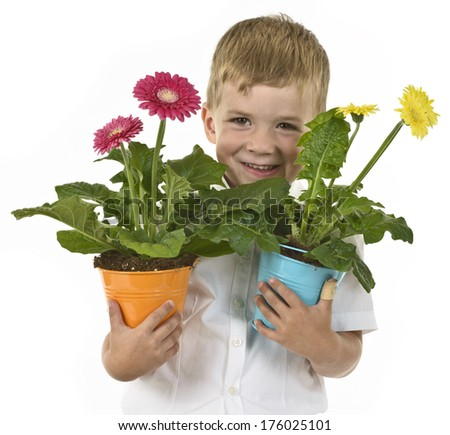 A young boy holding potted flowers in each hand.