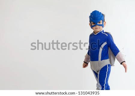 A Young Boy in a blue superhero suit with copy space - stock photo