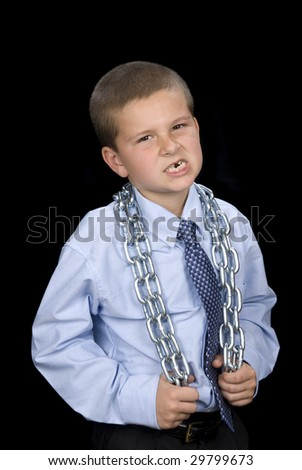 A young boy in a dress shirt and necktie has a chain around his shoulders and a serious look on his face.  Can be used for any business inference. - stock photo