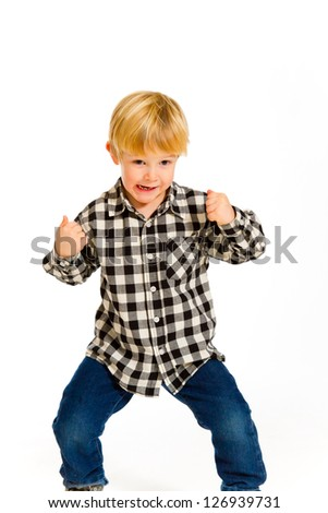 A young boy in a plaid shirt poses for this portrait in the studio against an isolated white background.