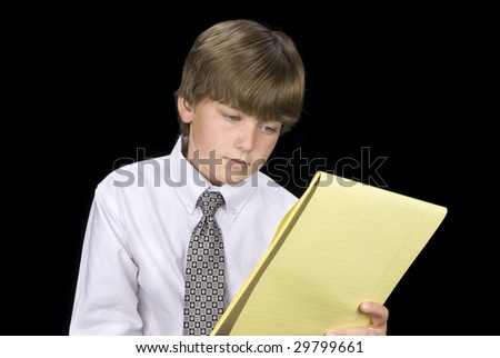 A young boy in formal business dress reads his notepad.  Image was shot against a black backdrop and can be used for any concepts and business inferences. - stock photo