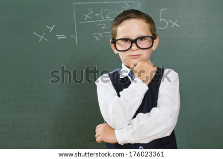 A young boy in front of a chalkboard. - stock photo