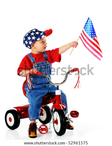 A young boy in red, white and blue happily displaying an American flag from his tricycle.  Isolated on white. - stock photo