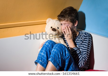 A young boy is crying on his bed in his bedroom - stock photo