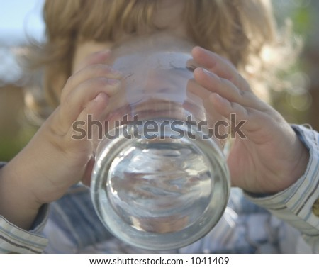a young boy is drinking a tall glass of water - stock photo