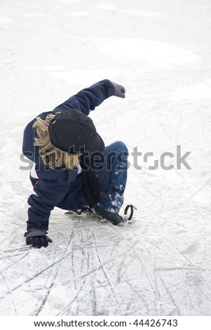 a young boy is falling on the ice, and loosing his ice-skate
