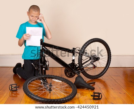 A young boy is frustrated by the instruction manual to assemble a new bicycle. - stock photo