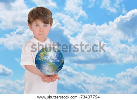 A young boy is holding the planet Earth in his hands and looks serious. There is a bright blue sky in the background and copyspace for text. - stock photo
