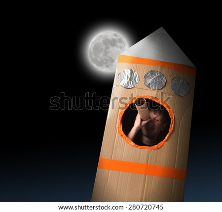 A young boy is in a cardboard space rocket ship pretending to be an astronaut and looking at the moon in the night sky. - stock photo
