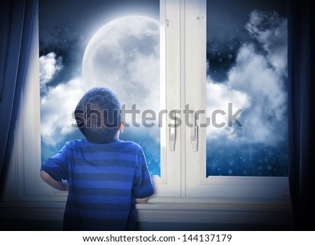 A young boy is looking out of the window at a big moon in the dark night with stars and space for an astronomy or imagination concept. - stock photo