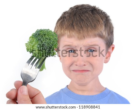 A young boy is making a funny disgusting face at a fork with a healthy piece of broccoli on a white background. - stock photo