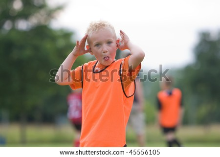 A young boy is making a funny face. - stock photo