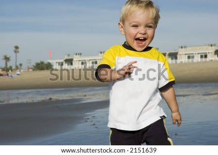 a young boy is playing at the beach - stock photo