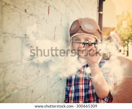 A young boy is pretending to be a pilot and playing with an airplane toy against a brick wall for a dream or career concept. - stock photo