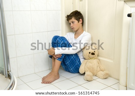 A young boy is sitting afraid and depressed in the corner of the bathroom with his bear - stock photo