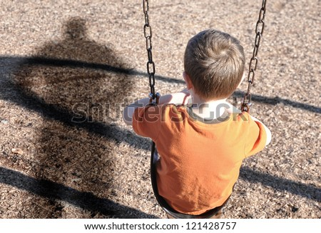 A young boy is sitting on a swing set and looking at a shadow figure of a man or bully at a playground. Use it for a kidnap, defense or safety concept.